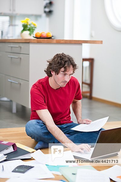 Mid-adult man working from home  using laptop on kitchen floor