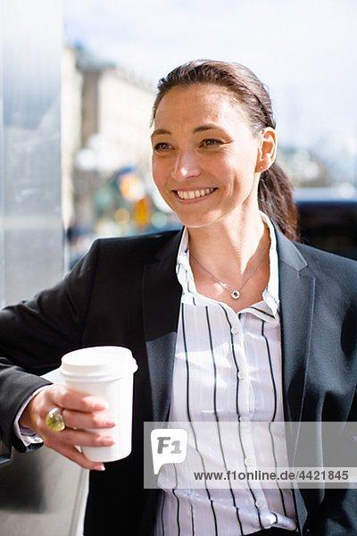 Porträt von fröhlich geschäftsfrau mit Takeaway Kaffee