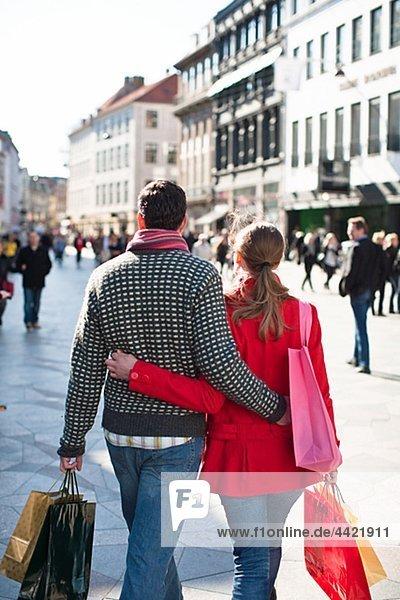 Paar mit Einkaufstaschen  zu Fuß in der Stadt