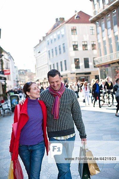 Mitte adult paar walking Street mit Einkaufstaschen