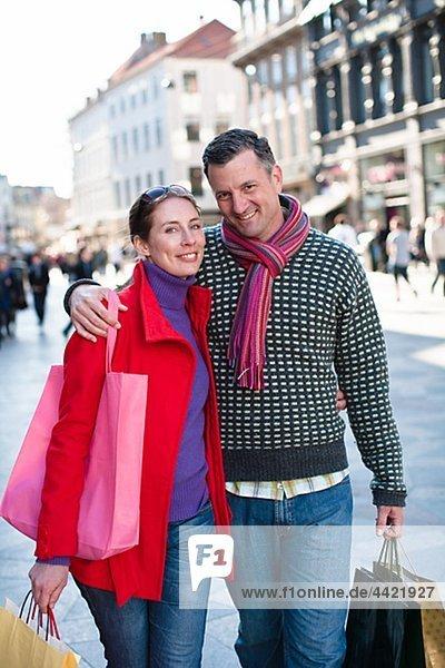 Mitte adult paar stehend auf Straße mit Einkaufstaschen