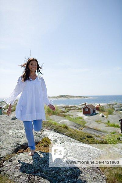 Woman walking on rock  smiling