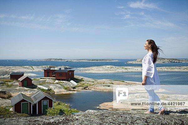Felsbrocken stehend Frau Gebäude Hintergrund