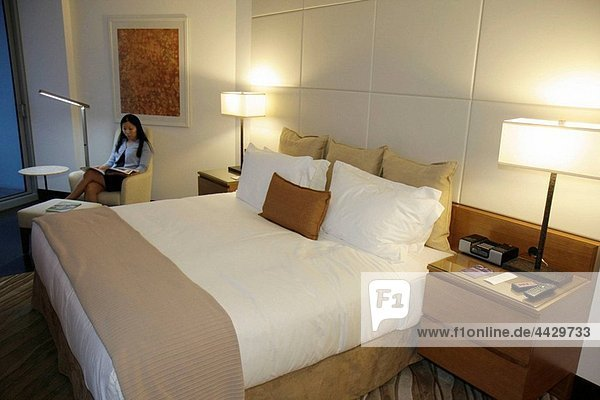 Florida  Miami  Epic Hotel  luxury  boutique  lodging  hospitality  guest room  bed  lamps  side tables  flat screen TV  modern decor  Asian  woman  reading  sitting