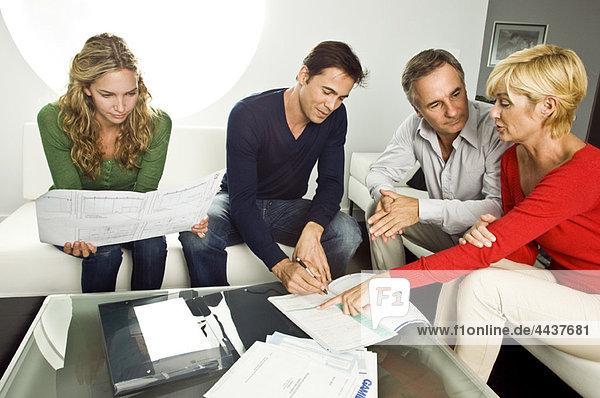 Junges Paar unterschreibt mit reifem Paar zu Hause