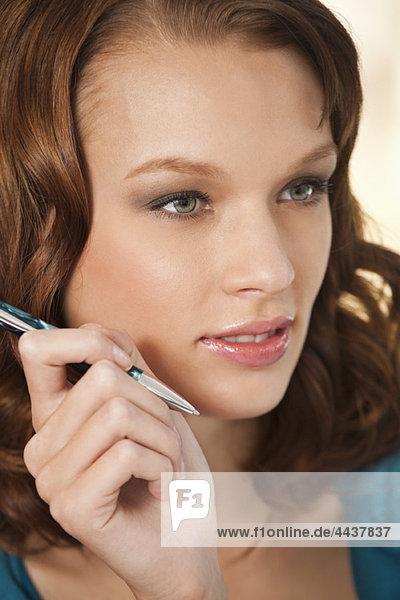 Eine junge Frau  die über etwas nachdenkt und einen Stift hält.