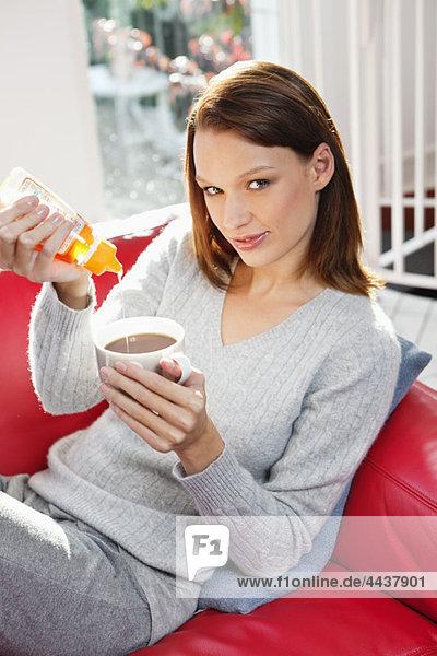Junge Frau gießt Honig in ihre Teetasse.