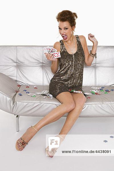 Junge glückliche Frau in formaler Kleidung  die Karten hält.