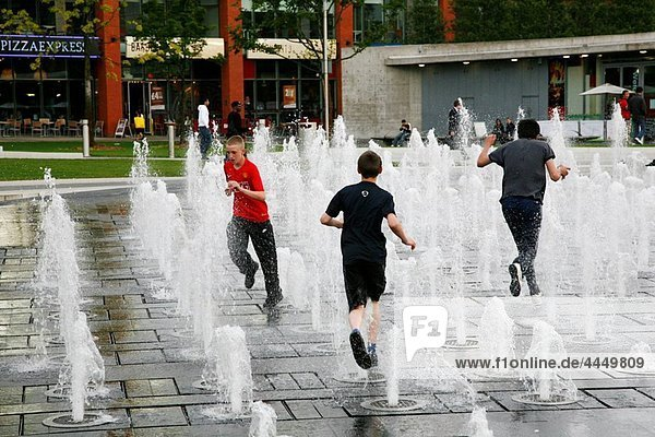 Young people playing in a fountain at Piccadilly Gardens  Manchester  England  UK