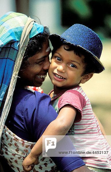 Woman carrying her child. Sri Lanka