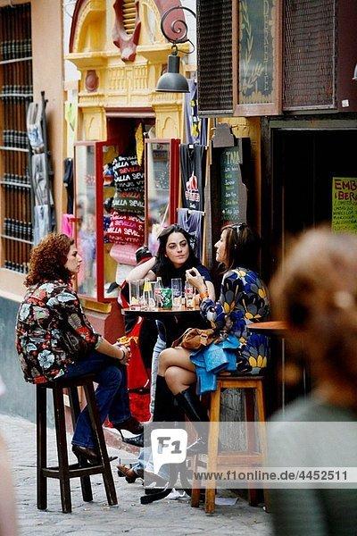 Three women sitting at a Bar Cafe in Barrio Santa Cruz  Seville  Spain.
