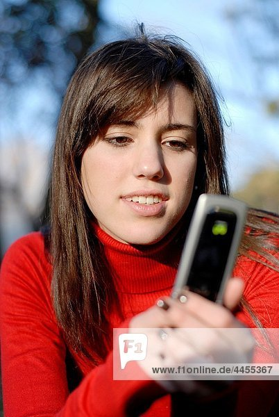 Portrait of a cute and sweet spanish teenager girl sending a message with her phone  in the park