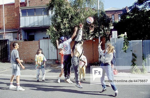 group of teenagers playing basketball in back street