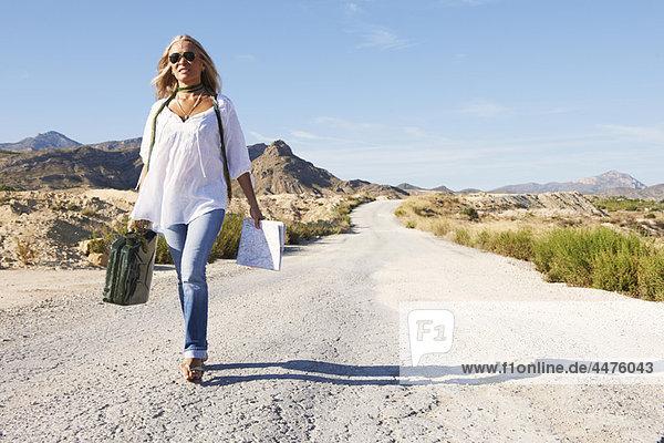 Frau geht alleine auf staubiger Straße