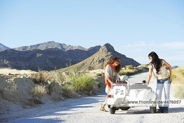 Frauen sitzen auf Motorrad und Beiwagen