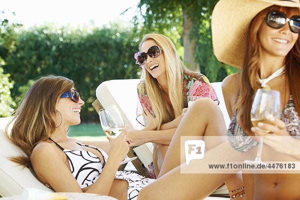 Mädchen entspannen am Pool auf Sonnenliegen
