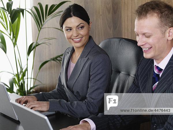 Geschäftsmann und Geschäftsfrau am Schreibtisch, Geschäftsmann und Geschäftsfrau am Schreibtisch