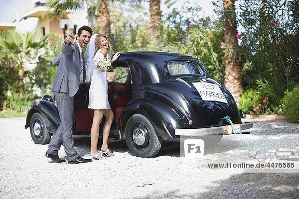 Brautpaar vor dem Auto