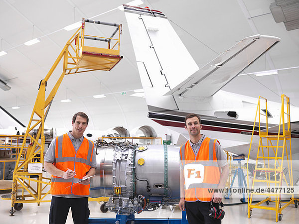 Engineers with jet engine in hangar