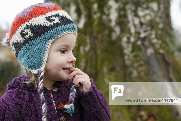 Little girl in knitted sweater and cap