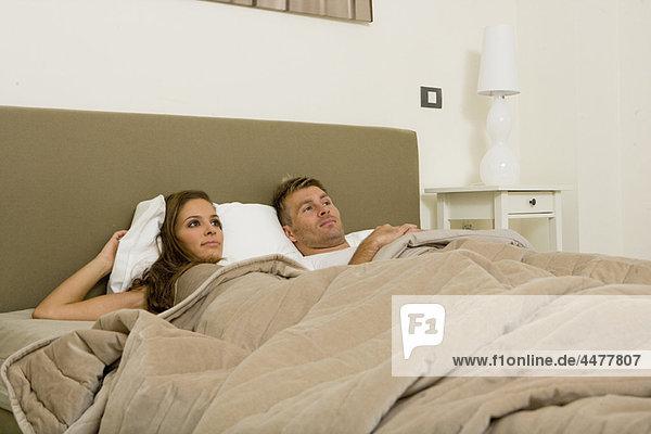 Junges attraktives Paar im Bett aufwachend