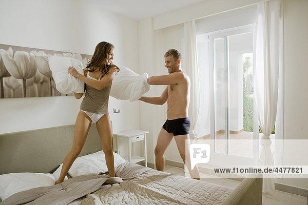 Junges Paar mit Kissenschlacht auf dem Bett
