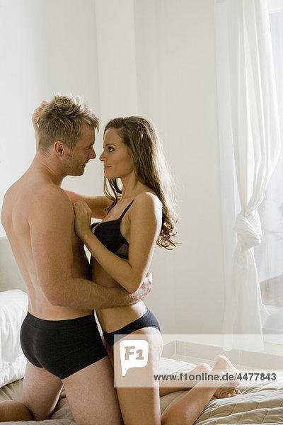 Junges halbnacktes Paar  das sich auf dem Bett umarmt