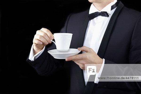 Mittelteil eines Mannes  der einen Smoking trägt und eine Tasse mit Untertasse hält.
