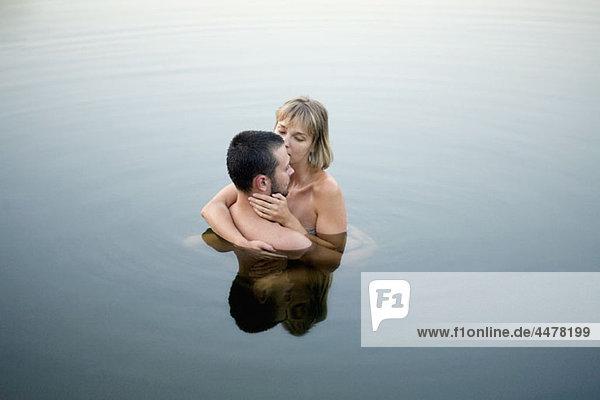 Paar im Wasser umarmend
