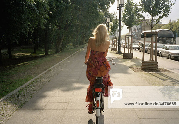Rückansicht einer Radfahrerin auf einem Fußweg