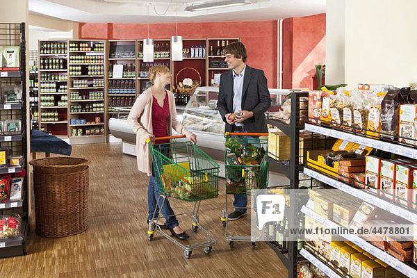 Ein Mann und eine Frau plaudern in einem Supermarkt.