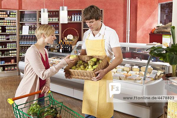 Ein Kunde und Lebensmittelhändler in einem Supermarkt
