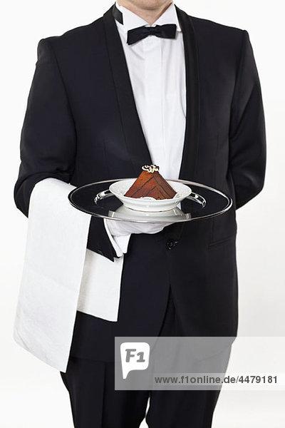 Ein Butler hält ein Stück Kuchen auf einem Silbertablett  Mittelteil