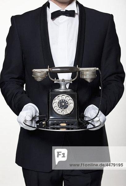 Ein Butler hält ein antikes Drehtelefon auf einem silbernen Tablett  Mittelteil