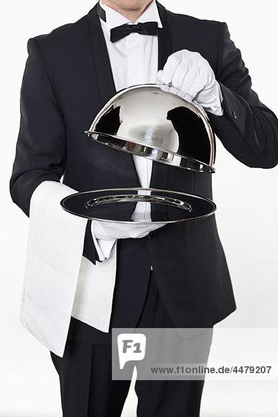 Ein Butler  der den gewölbten Deckel von einem leeren Silbertablett nimmt.