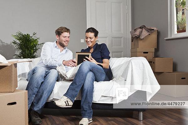Ein Paar sitzt auf einem Sofa und schaut auf einen Bilderrahmen.