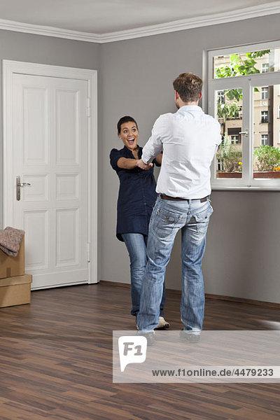 Ein Mann und eine Frau  die Händchen halten und in ihrem neuen Zuhause herumschwingen.