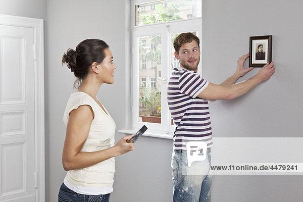 Ein Paar hängt einen Bilderrahmen in seinem neuen Zuhause auf.
