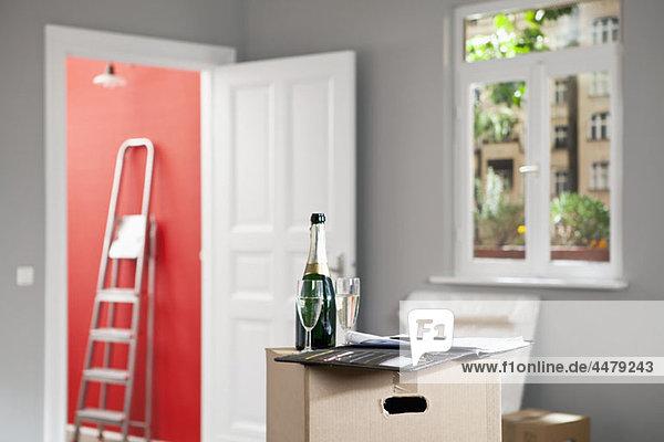 Champagner und ein Vertrag im Wohnzimmer mit Umzugskartons