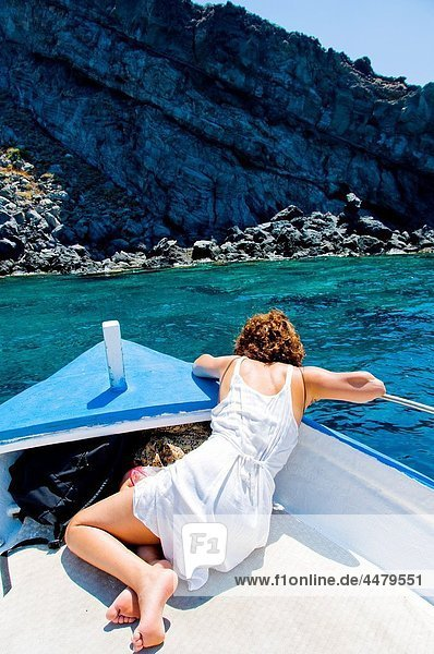 Woman leaning overboard on boat looking at the sea water Pantelleria island  Sicily  Italy