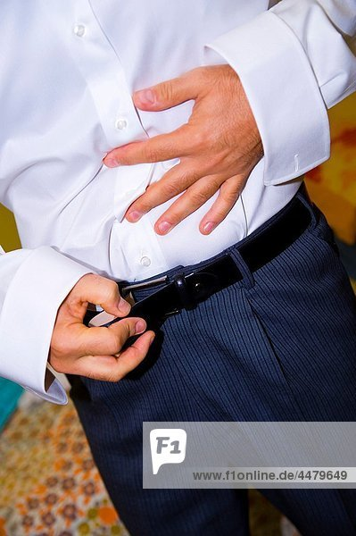 Cropped view of man putting on a belt