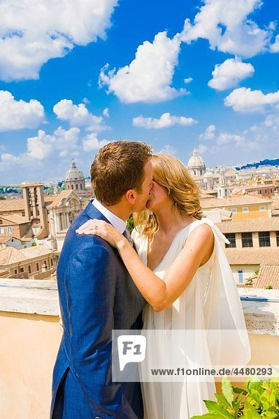 Young bride and groom kissing on rooftop in Rome  Italy