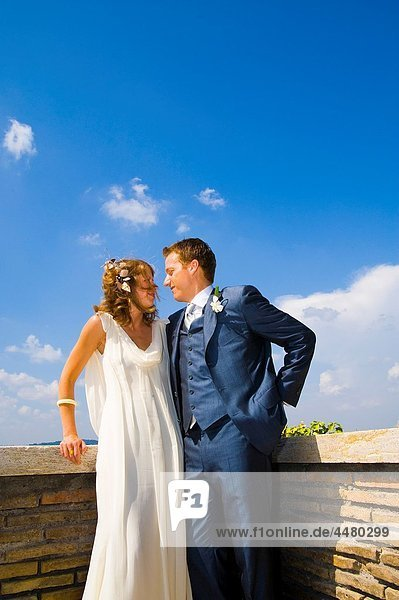 Young bride and groom standing on terrace in Rome  Italy