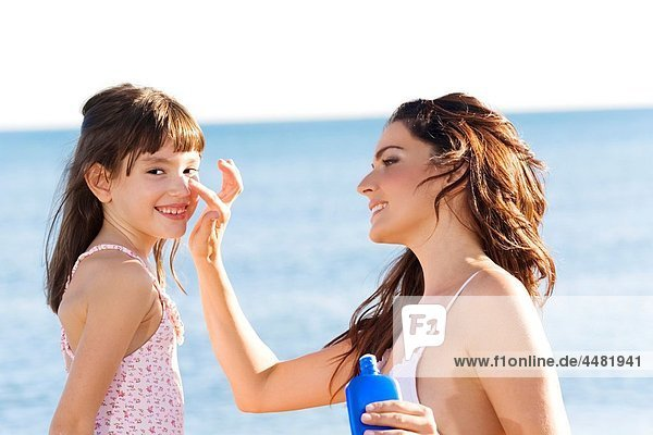 Mother applying sun protection cream to her daughter