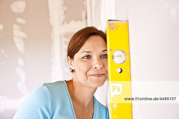 Frau hält Wasserwaage an Wand