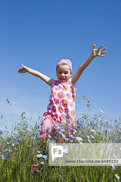 Mädchen läuft über eine Blumenwiese