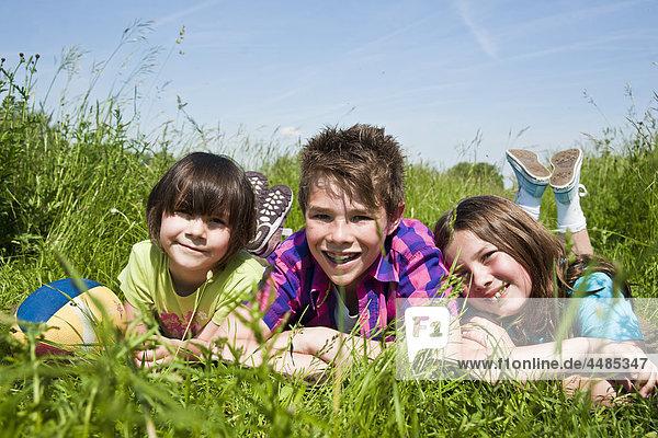Drei Kinder liegen auf einer Wiese