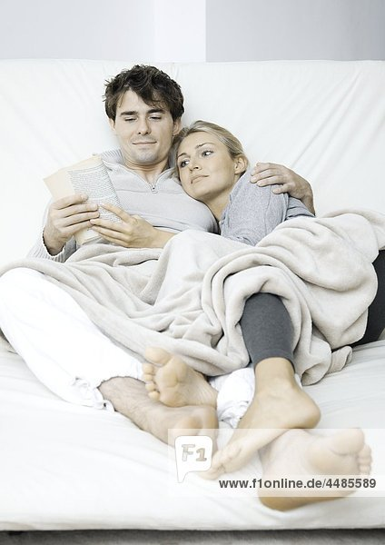 Junges Paar im Bett liest ein Buch