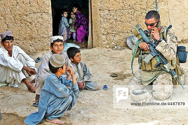 Lance Cpl Jack Hamilton  a rifleman with Golf Company  2nd Battalion  9th Marine Regiment  calls his position in to headquarters while taking a rest to play with some curious Afghan children during a census operation in Marjah  Afghanistan  Aug 16 The
