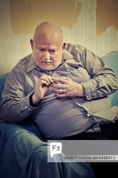 Balding  middle-age man sitting on a sofa